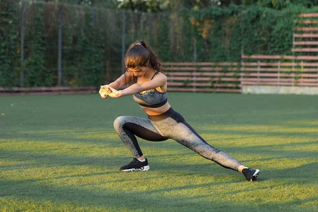 A young slim athletic girl in sportswear with snakeskin prints performs a set of exercises. fitness and healthy lifestyle.