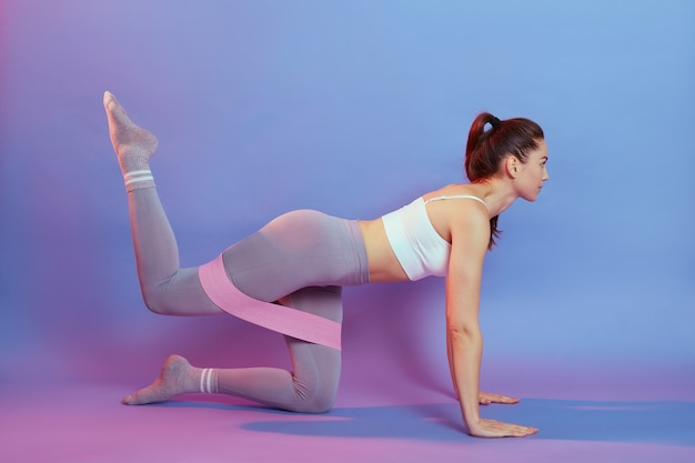 Young slim attractive female wearing white top and gray leggins posing on floor on knees, raising legs, using rose fitness rubber band, isolated over blue and rose wall.