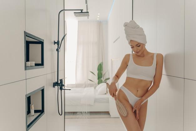 Молодая стройная привлекательная девушка делает антицеллюлитный массаж деревянной щеткой, принимая душ в ванной комнате на фоне современного стильного интерьера спальни. концепция красоты и гигиены женщин