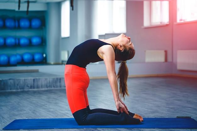 Молодая стройная привлекательная женщина с длинными волосами, практикующая йогу в помещении