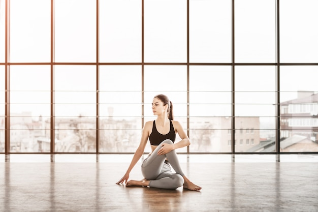 Young slim attractive woman with long hair practicing yoga indoors.