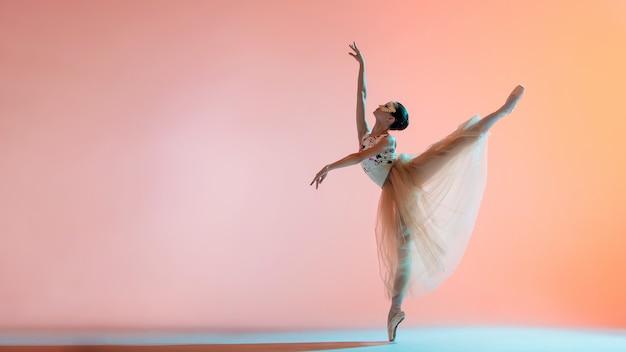 밝은 긴 드레스를 입은 젊은 슬림 발레리나가 백라이트가있는 컬러 배경에서 춤을 추고 있습니다.