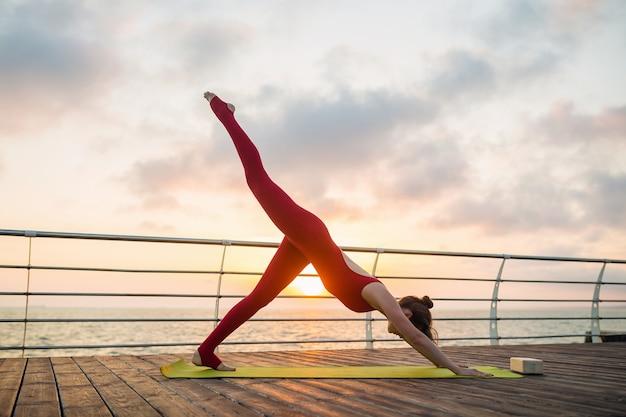 Молодая стройная красивая привлекательная женщина занимается йогой утром на восходе солнца у моря, здоровый образ жизни