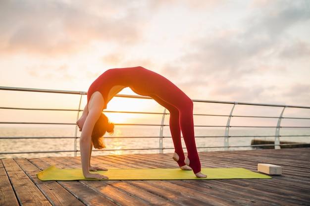 海、健康的なライフスタイルで日の出の朝にヨガをやっている若いスリムな美しい魅力的な女性