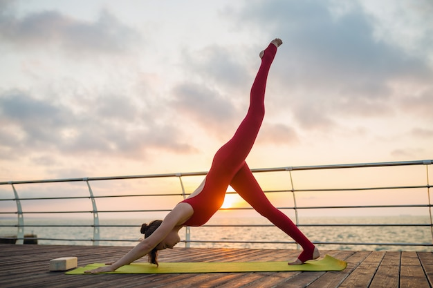 Young slim beautiful attractive woman doing yoga in the morning on sunrise by sea, healthy lifestyle