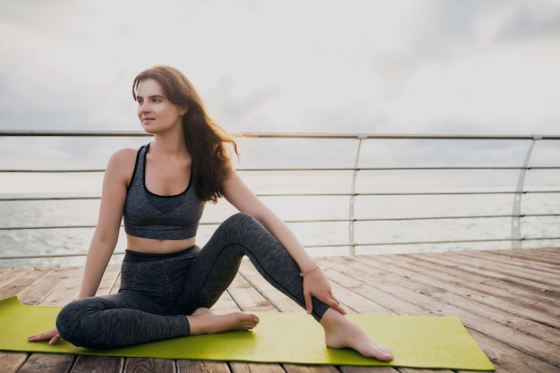 Young slim beautiful attractive woman relaxing on yoga mat in the morning on sunrise by sea, healthy lifestyle, fitness sport