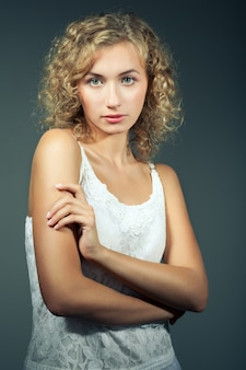 Young slim beautiful blond woman with curly hair in white sexy dress standing and looking at camera over grey background