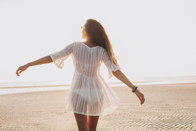 Молодая стройная красивая женщина на пляже заката
