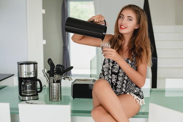 キッチンに座っている若いスリムな美しい女性
