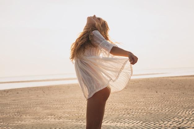 Giovane bella donna sottile sulla spiaggia al tramonto
