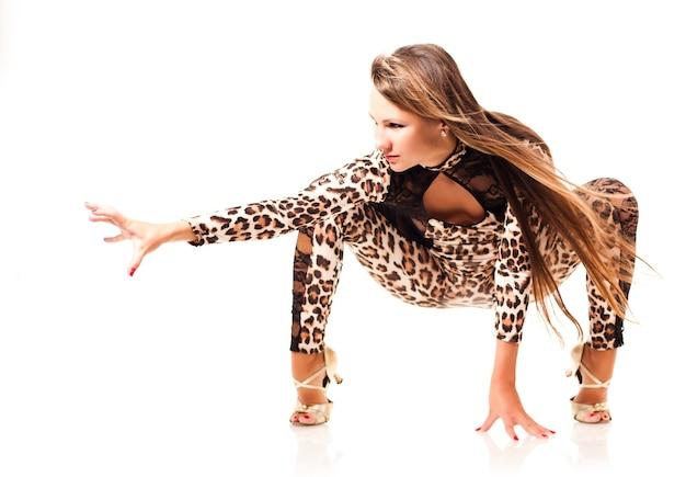 白い背景の上に猫のポーズで座っているセクシーなヒョウ柄の衣装で長い髪の若いスリムな美しい女性