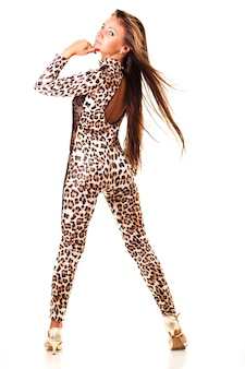 白い背景の上に立っているセクシーなヒョウ柄の衣装で長い髪の若いスリムな美しい女性