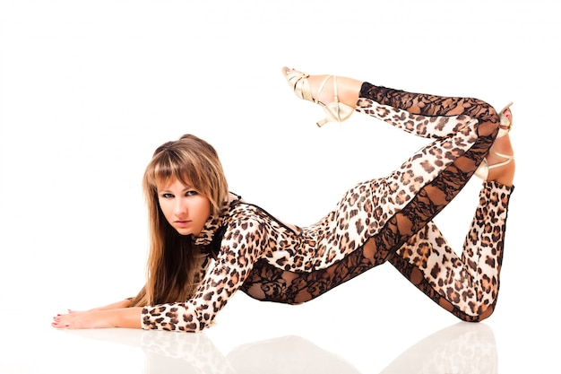 Young slim beautiful woman with long hair in  leopard printed costume sitting in cat pose over white background