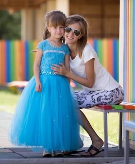 若いスリムなブロンドの笑顔の母親、叔母または妹は、遊び場の背景をぼかした写真に長い素敵な青いイブニングドレスの小さなかなり就学前の娘の女の子を抱擁します。幸せな家族関係と愛の概念。