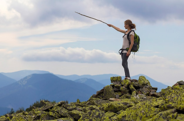 Young slim blond tourist girl with backpack points with stick at foggy mountain range panorama standing on rocky top on bright blue morning sky scene. tourism, traveling and climbing concept.