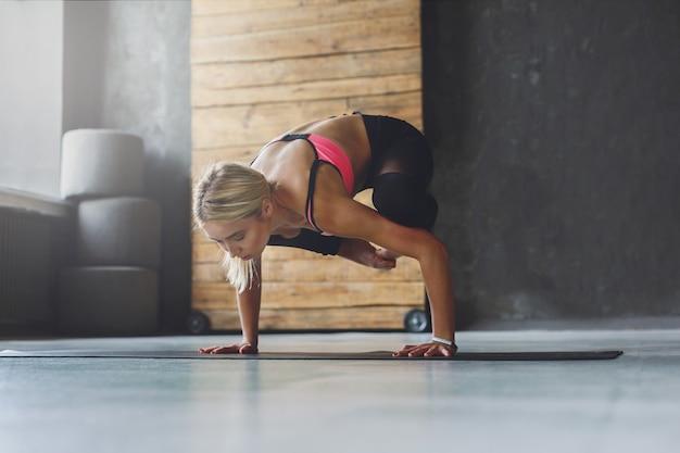Молодая стройная блондинка женщина в классе йоги, делая упражнения асаны. женщина делает позу крана. здоровый образ жизни в фитнес-клубе. растяжка