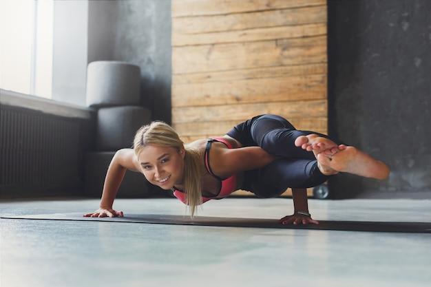 Молодая стройная блондинка женщина в классе йоги, делая упражнения асаны. женщина выполняет позу восьмиугольника, аштавакрасану. здоровый образ жизни в фитнес-клубе. растяжка