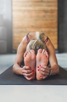 Молодая стройная блондинка женщина в классе йоги, делая упражнения асаны. женщина делает сидящую позу наклона вперед. здоровый образ жизни в фитнес-клубе. растяжка. селективный акцент на пятке ног