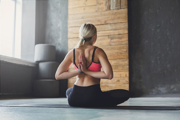 Young slim blond woman in yoga class making asana exercises. woman do reverse prayer pose, back and shoulders stretching. healthy lifestyle in fitness club.