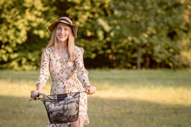 Young, slim, blonde woman on bicycle against defocused park landscape. autumn color shade.