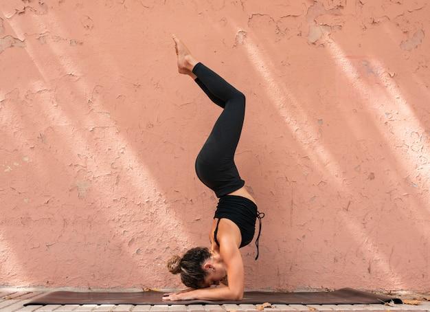Молодая стройная блондинка в классе йоги, делая красивые асаны. поза русалки, вариация раджакапотасаны. растяжка здорового образа жизни