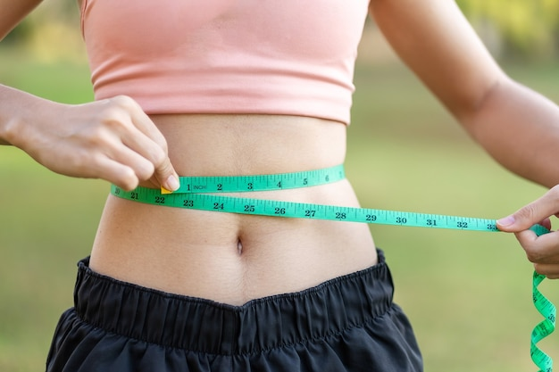 Young slim body female in pink sportswear, healthy woman measuring her thin waist.