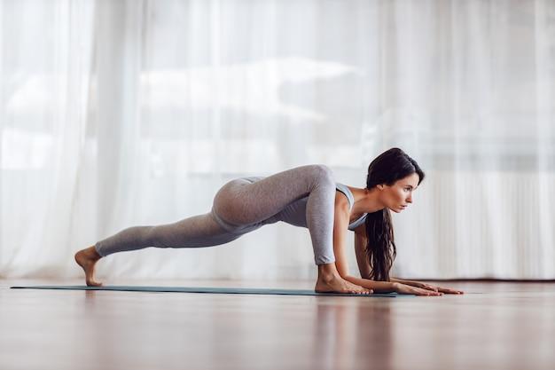 Young slim brunette in lizard yoga position. yoga studio interior.