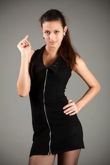 灰色の上に立っているセクシーな黒のミニドレスと網タイツの若いスリムなブルネットの女性モデル