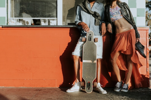 Young slim couple posing with a longboard