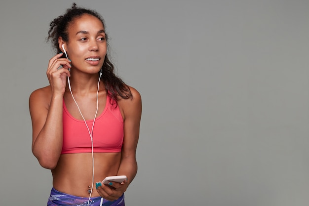 Young slim curly long haired brunette lady with dark skin inserting earpiece into her ear and looking aside with pleasant smile, relaxing after gym