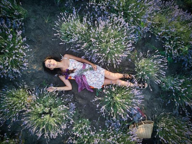 Молодая стройная светлокожая девушка брюнетка красивая лежит в лавандовом поле. вид сверху.