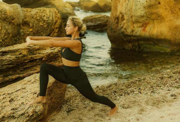 野生のビーチで石の上で体操のアーサナ運動をしているスポーツウェアの若いスリムフィットの女性。準備し始める。