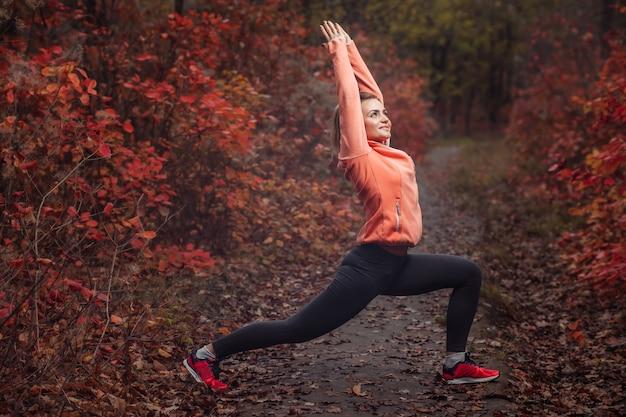 Молодая стройная женщина в спортивной одежде занимается упражнениями асана-йоги в осеннем лесу