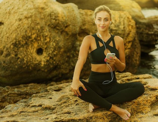 野生のビーチの石の上に座ってイヤホンで音楽を聴き、スマートフォンを使用してスポーツウェアの若いスリムフィット女性