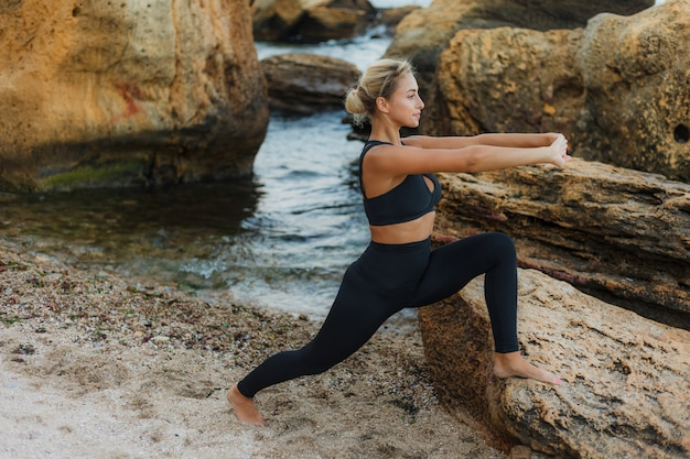 Young slim fit woman in sportswear doing gymnastic asana exercise on stone at wild beach. warm up.