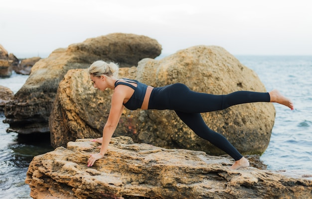 Young slim fit woman in sportswear doing gymnastic asana exercise on stone at wild beach