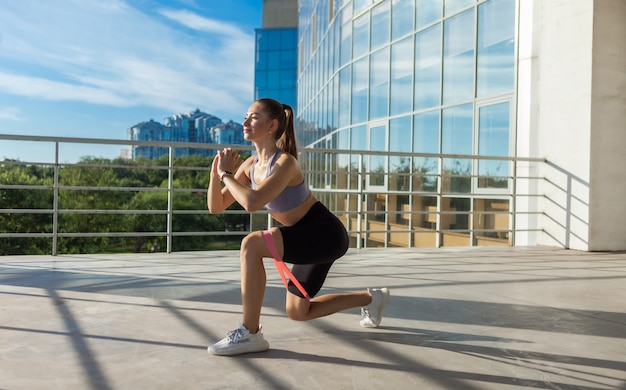 도시에서 야외에서 피트니스 고무 밴드로 운동하는 젊고 날씬한 여성
