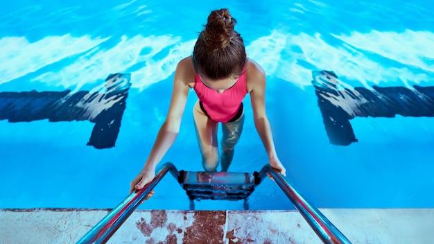 Молодая тонкая женщина пловца фитнеса в купальнике используя лестницу бассейна во время плавать в бассейне спортов в центре отдыха. заниматься спортом и вести здоровый образ жизни.