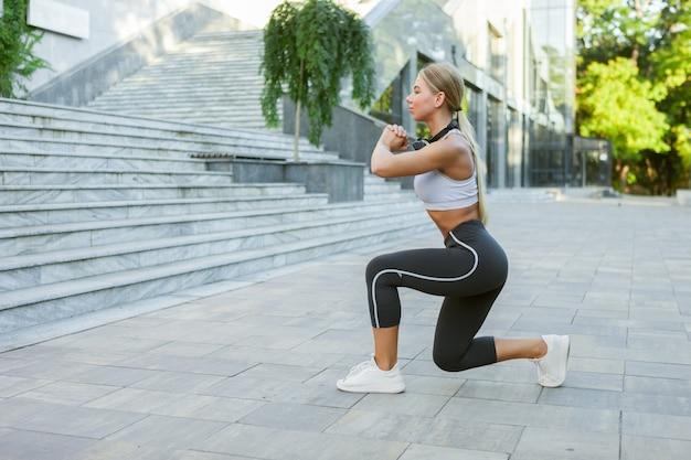야외에서 훈련하기 전에 다리 스트레칭과 워밍업 운동을 하는 운동복을 입은 젊은 슬림 피트니스 여성