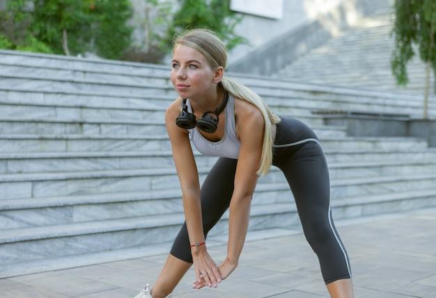 야외에서 훈련하기 전에 스트레칭과 워밍업 운동을 하는 운동복을 입은 젊은 슬림 피트니스 여성