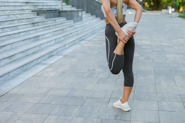 야외에서 훈련하기 전에 다리를 위한 스트레칭과 워밍업 운동을 하는 운동복을 입은 젊은 슬림 피트니스 여성