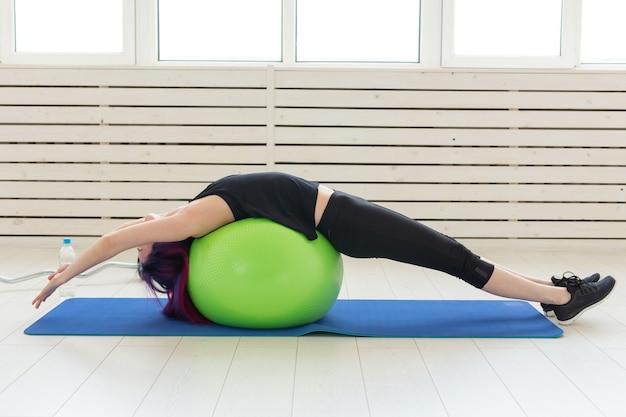 若いスリムな女の子は、明るいジムで緑のフィットボールで背中の運動とストレッチを行います。健康的な背中と靭帯の概念。