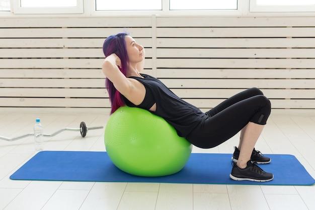 Молодая стройная девушка делает упражнения и растягивается для спины на зеленом фитболе в ярком спортзале