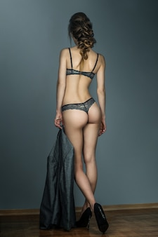 Young slim girl on high hills in lace underwear with sexual round buttocks posing in studio