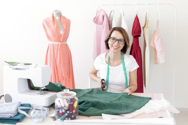 眼鏡をかけている若いスリムな女の子の仕立て屋のデザイナーは、ミシンの糸で彼女の机に座って、新製品を縫うために生地を切ります。縫製ワークショップのコンセプト。