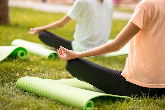 若いスリムな女の子は、暖かい日に公園の緑の芝生で他の女の子と一緒にヨガマットでエクササイズをしている蓮華座でリラックスして座っています。 。