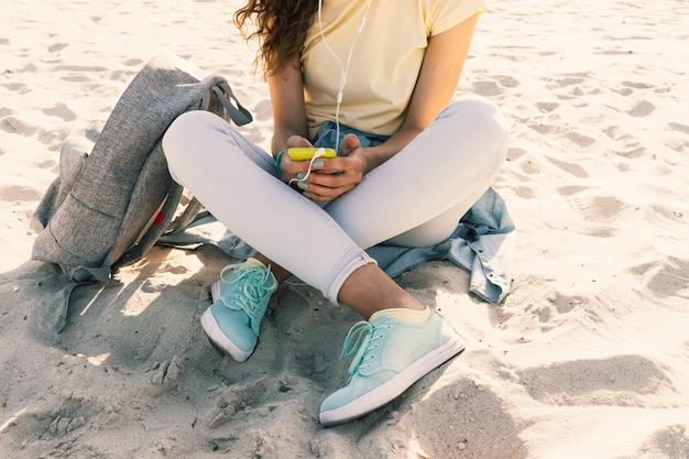 Young slim girl sitting on the beach in jeans and a yellow t-shirt and listening to music