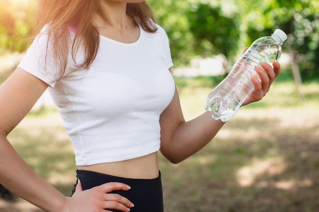 Young slim girl in a white t-shirt holding a bottle of mineral water.