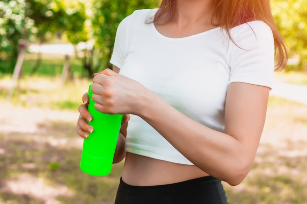 Young slim girl in a white t-shirt holding a sports bottle in her hand.