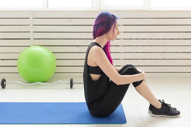 色付きの髪の若いスリムな女の子は、バーベルと緑のフィットボールの横にあるスポーツの青いマットレスに逆立ちします。優れた体力とジムでの定期的なトレーニングの概念。